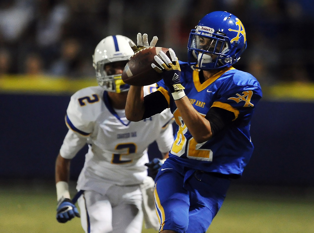 Description of . Bishop Amat's Brandon Arconado (82) catches a pass for a first down ahead of Charter Oak's Candy Nava (2) in the first half of a prep football game at Bishop Amat High School in La Puente, Calif. on Friday, Sept. 20, 2013.    (Photo by Keith Birmingham/Pasadena Star-News)