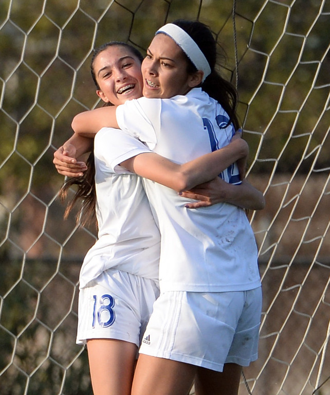 Description of . Bishop Amat's Ashley Rushlow (18) is hugged by teammate Jamie Peters after scoring against Marshall in the first half of a prep soccer match at Bishop Amat High School in La Puente, Calif., on Thursday, Jan. 9, 2014.Amat won 3-0. (Keith Birmingham Pasadena Star-News)