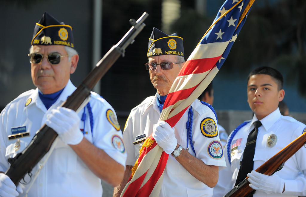 Description of . The city of Norwalk and the Norwalk American Legions Post No. 359 observe Veterans Day with a ceremony at Norwalk City Hall on Monday, November 11, 2013.  American Legion member Frank Brown, center, carries the American flag as the legionaires color guard starts off the ceremony to post the colors. (Photo by Scott Varley, Daily Breeze)