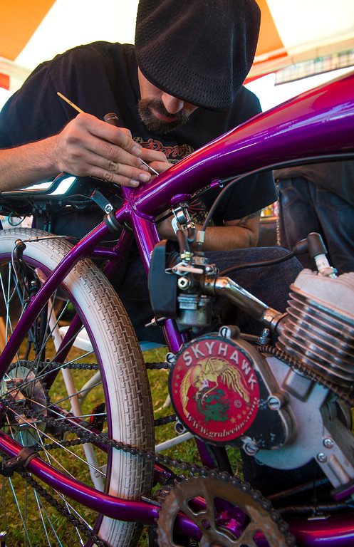 Description of . IDB-L-DBROUTE66-SAT-018 Isidro Aguilar, of Hot Rod Pinstriping Circus, works on a pinstripe design  on a motorized bicycle, at  the