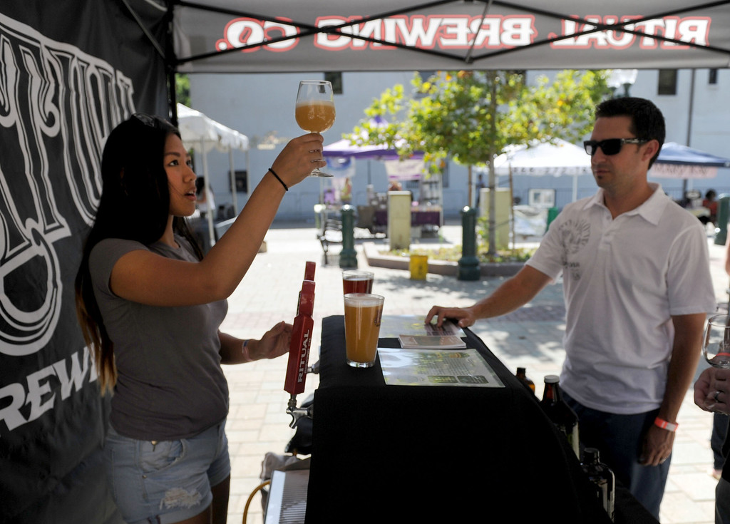 Description of . (John Valenzuela/Staff Photographer)  Adrienne Macalinao of Ritual Brewery, pours a glass of beer for Mark Martinez of Redlands during the Redlands Wine, Beer, and Music event at Ed Hales Park in downtown Redlands, Saturday, June 22, 2013.