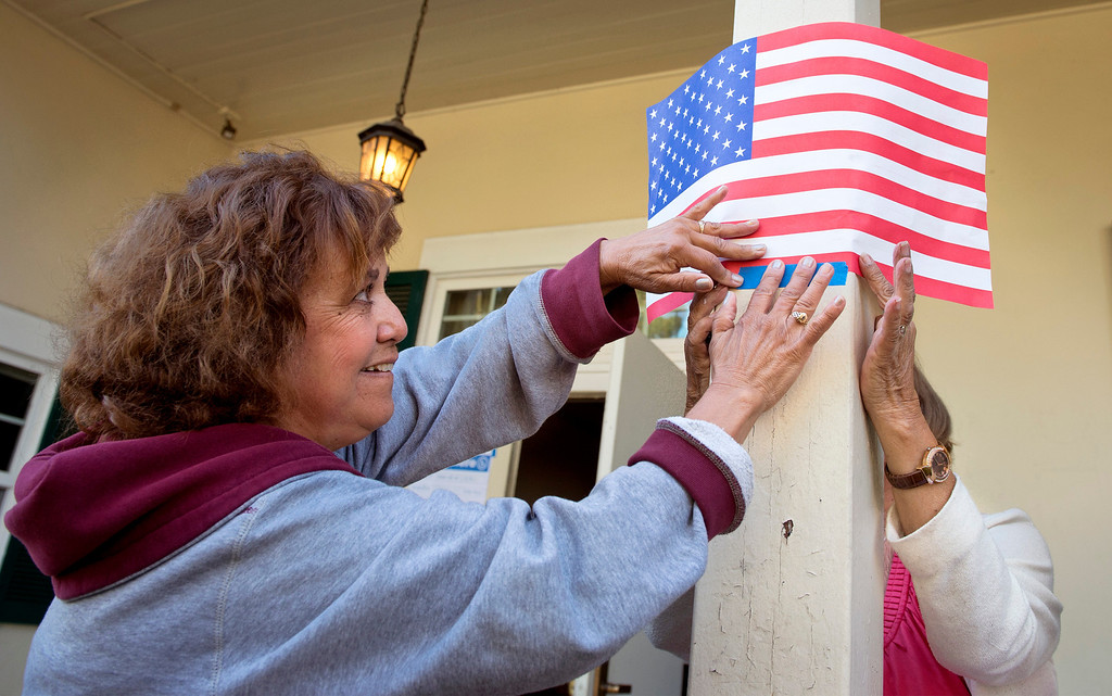 Description of . Poll worker Gloria Gomez tapes up a flag marking the polling entrance at the Greenleaf Masonic Temple on Beverly Boulevard in Whittier, Calif. Tuesday morning June 3, 2014.   (Staff photo by Leo Jarzomb/Whittier Daily News)