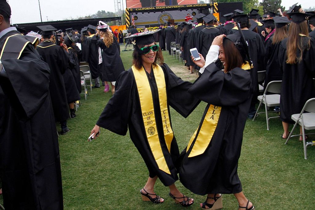 Description of . Mae Dizon, left, and Sophea Nguon, both of Los Angeles, during the  California State University, Los Angeles, Sixty-Sixth Graduate and Undergraduate Commencement Ceremony, at California State University Athletic Stadium, in  Los Angeles, Saturday, June 15, 2013. (Correspondent Photo by James Carbone/SXCITY)