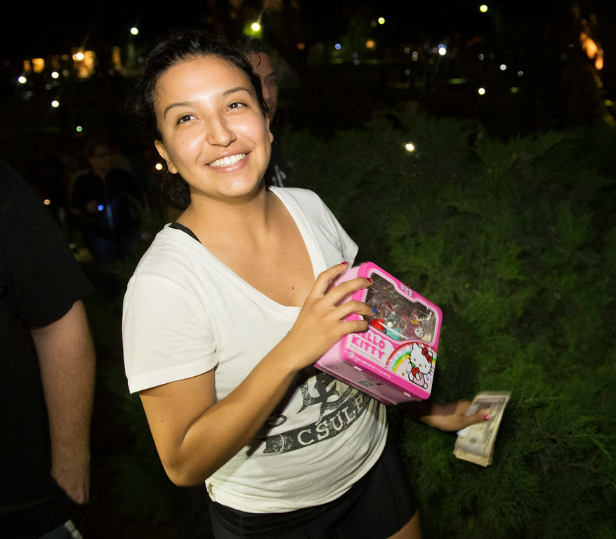 Description of . Alejandra Garcia, of Whittier, shows the Hello Kitty lunchbox she found with $100 as cash hunters search all over Penn Park in Whittier for #HiddenCash stashed in Pez dipsensers and lunch boxes in the park bushes on Thursday July 10, 2014. Hundreds of people searched through the bushes all over the park. (Staff Photo by Keith Durflinger/Pasadena Star-News)