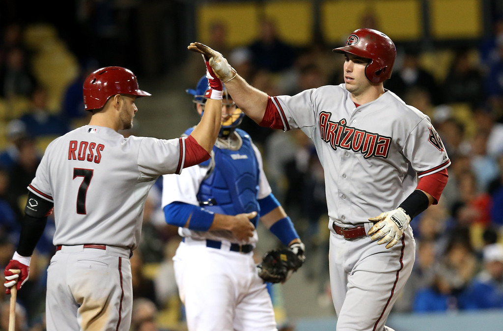 Description of . Paul Goldschmidt #44 of the Arizona Diamondbacks is greeted by on deck batter Cody Ross #7 after Goldschmidt's two run home run against the Los Angeles Dodgers at Dodger Stadium on May 6, 2013 in Los Angeles, California.  Ross then followed with a home run of his own.  Diamondbacks won 9-2.   (Photo by Stephen Dunn/Getty Images)