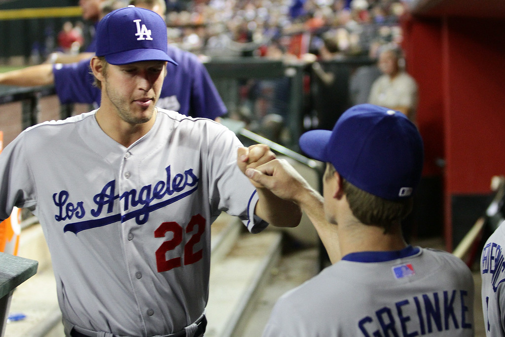 Description of . Clayton Kershaw #22 and Zach Greinke #21 of the Los Angeles Dodgers fist bump in the sixth inning against the Arizona Diamondbacks at Chase Field on April 12, 2014 in Phoenix, Arizona.  (Photo by Jason Wise/Getty Images)