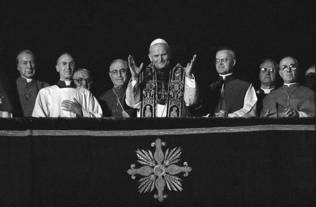Description of . Pope John Paul II greets the cheering crowd from the balcony of St. Peter's Basilica in Vatican City, Monday evening, Oct. 16, 1978, shortly after his election to succeed the late Pope John Paul I, Oct. 16, 1978.  The new head of the Catholic Church, the former archbishop of Krakow, Poland, Karol Cardinal Wojtyla, is the first non-Italian since 450 years. The pontiff is flanked by, from left to right, Polish Cardinal Stefan Wyszynski; Msgr. Orazio Cocchetti of the pontifical ceremonies office; cardinal Bertoli of Italy; cardinal Siri of Italy; and Msgr. Virgilio Noe of the pontifical cermonies office.  (AP Photo)