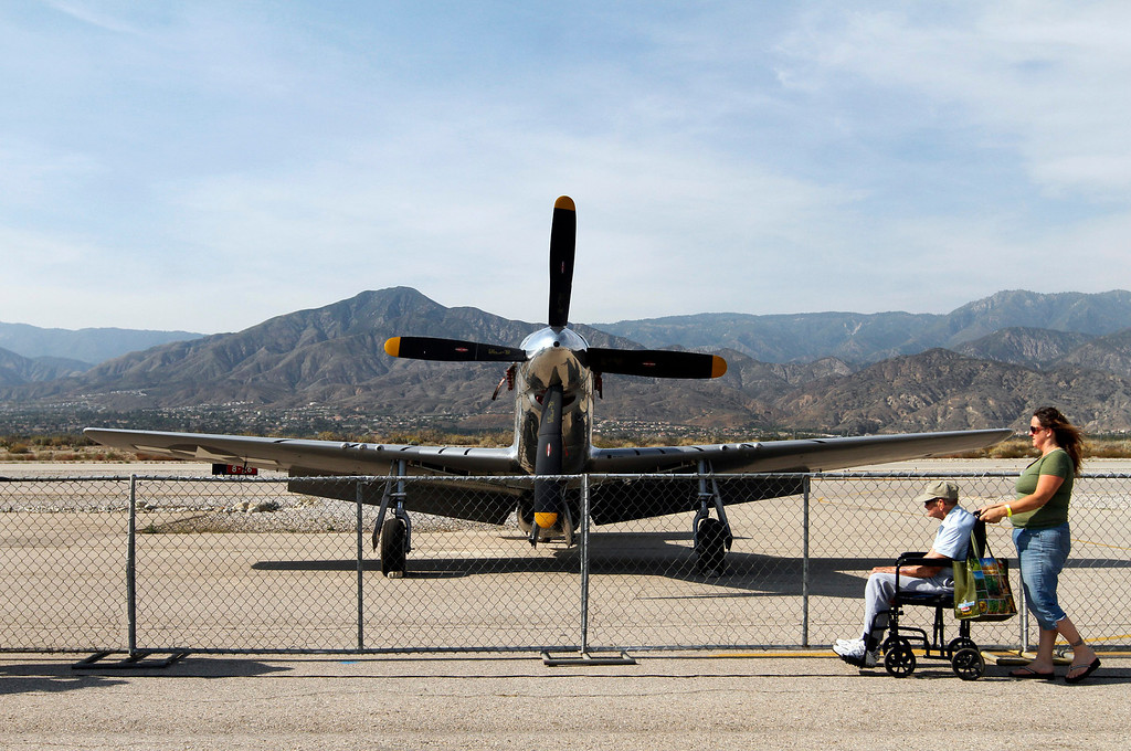 Description of . Diane Hurtado, 47, right, wheels her grandfather Frank Robison, 95, of Redlands, to a stop in front of a P-51 Mustang at the Hangar 24 AirFest and 6th Anniversary Celebration on Friday, May 16, 2014 at the Redlands Municipal Airport in Redlands, Ca. Hurtado says Robison served in World War II and flew 87 missions in a P-51 which is the plane they specifically visited the AirFest to see. (Photo by Micah Escamilla/Redlands Daily Facts)
