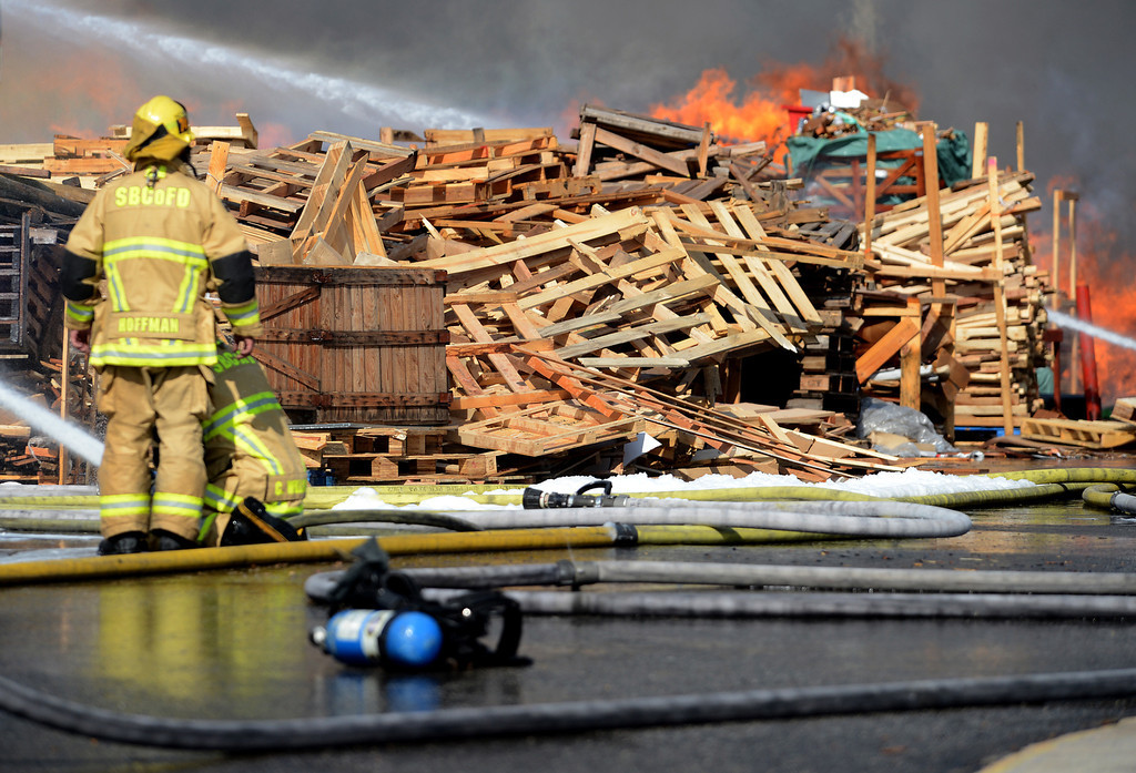 Description of . Firefighters battle a five alarm fire Saturday, May 4, 2013, at a pallet yard in the 8300 block of Sultana Avenue in Fontana. Jennifer Cappuccio Maher/Daily Bulletin