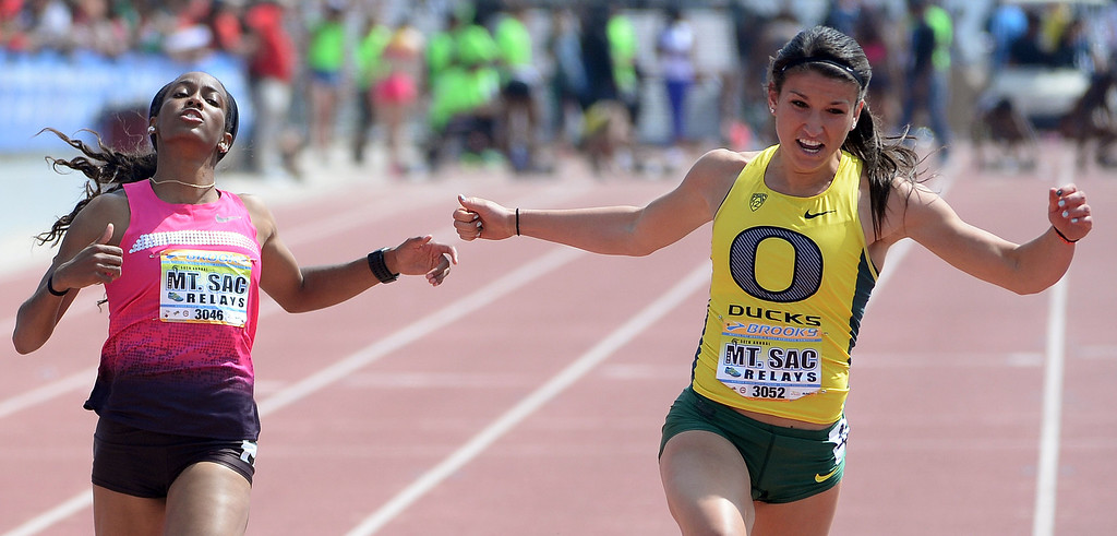 Description of . Oregon's Jenna Prandini, right, wins the 100 meter Dash Invitational Elite during the Mt. SAC Relays in Hilmer Lodge Stadium on the campus of Mt. San Antonio College in Walnut, Calif., on Saturday, April 19, 2014. 