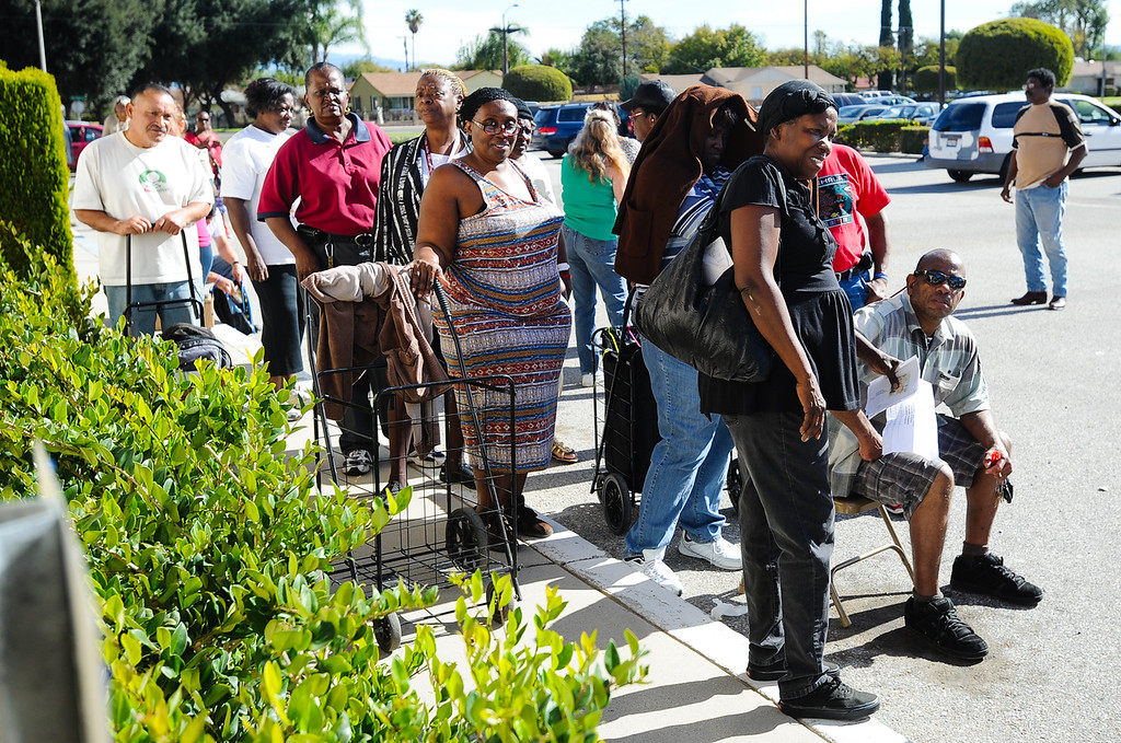 Description of . Families wait to receive free Thanksgiving dinner baskets at 16th Street Seventh-day Adventist Church in San Bernardino on Tuesday, Nov. 26, 2013. The church distributed 175 baskets to families-in-need. (Photo by Rachel Luna / San Bernardino Sun)