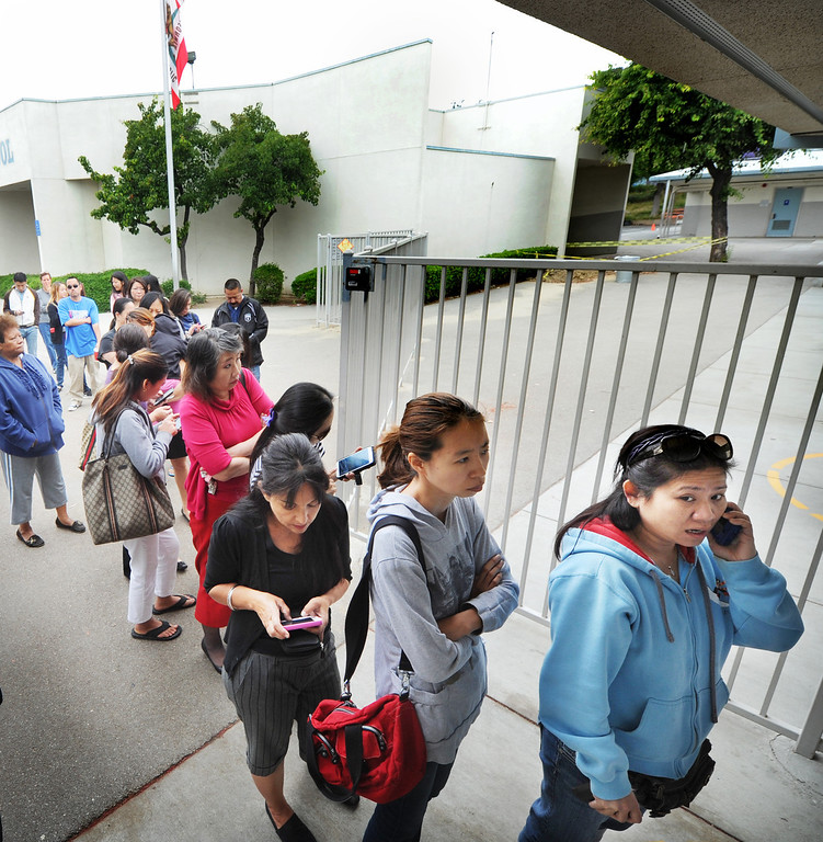 Description of . Concerned parents lining outside the entrance of the Brightwood School office in Monterey Park, waiting for children to be released from a lockdown at the school. A 19-year-old man was arrested for allegedly making phone calls to the California Highway Patrol threatening gun violence against local schools on Thursday, May 16, 2013. When the suspect called to make the threat, he said he was en route to a college in Monterey Park, she said. The call was made from a cell phone and was received from the East Los Angeles and Monterey Park areas, officials said.About 14 schools were locked down during the incident. At about 9:30 a.m., Santa Monica Community College police arrested a suspect, a 19-year old male in connection with this threat as well as the Santa Monica threat,