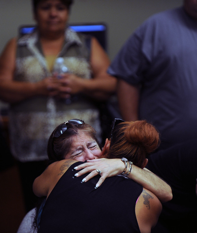 Description of . (8-22-13)--SAN BERNARDINO-- Rosie Curonilla,left, mother of Daniel Olivera is comfort by a family memeber  after watching a surveillance footage of her son death during a press conference at the San Bernardino County Sheriff's Headquaters Thursday August 22, 2013 in San Bernardino. Daniel Olivera 26, of Hesperia was shot and killed at the AM/PM Arco convenience store on August 11, 2013 in Victorville.LaFonzo Carter/Staff Photographer