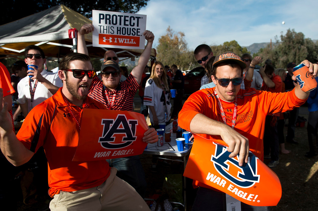 Description of . Auburn fans dance in the parking lot before the BCS National Championship game at the Rose Bowl in Pasadena Calif. on Monday, Jan. 6, 2014. (Watchara Phomicinda/ Pasadena Star-News)