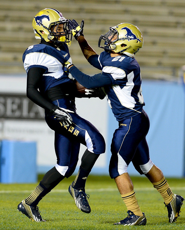 Description of . Muir 's Tony Claxton (21) celebrates Daniels Cervantes (5)  first touchdown of the annual Turkey Tussle against Pasadena Friday night, November 8, 2013 at the Rose Bowl in Pasadena. (Photo by Sarah Reingewirtz/Pasadena Star-News)