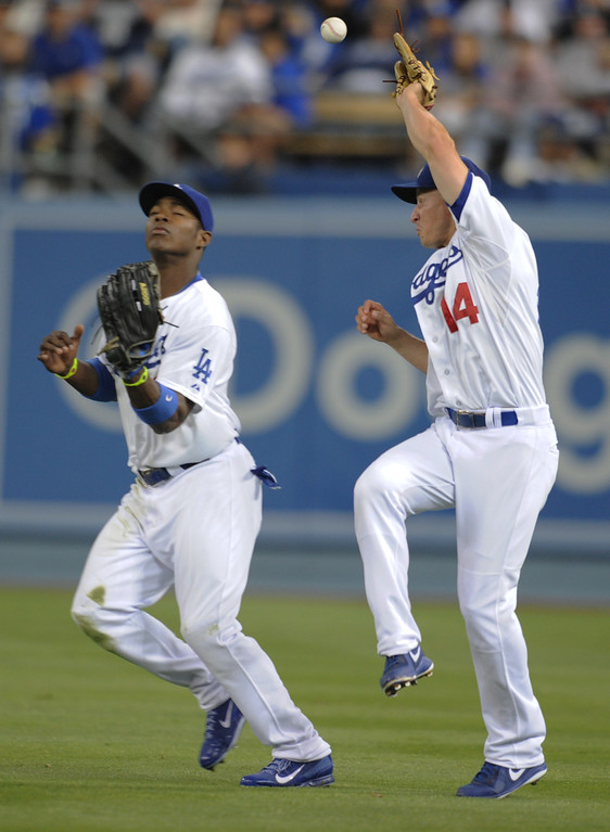 Description of . Mark Ellis looks over at Yasiel Puig after the two of them nearly collided in the 9th inning. The Dodgers were defeated 3-0 by the New York Yankees in a game at Dodger Stadium in Los Angeles, CA. 7/31/2013 (John McCoy/LA Daily News)