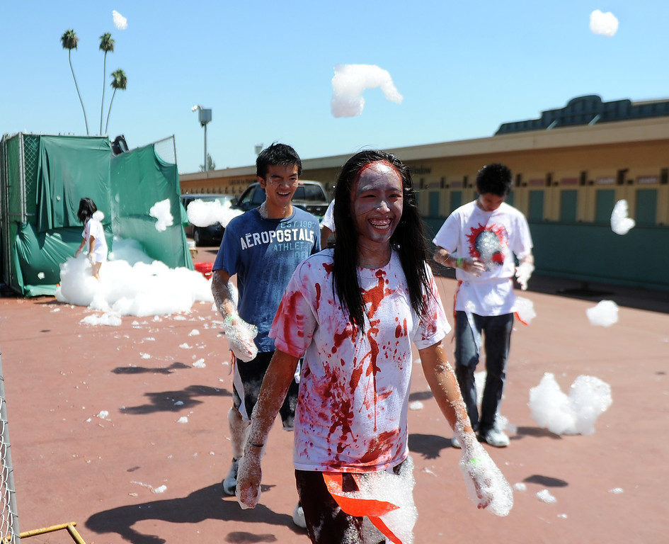 Description of . Runners finish the race running through a foam bath during the Zombie Blood Run at Santa Anita Park on Saturday, Aug. 17, 2013 in Arcadia, Calif. The American Red Cross San Gabriel Pomona Valley chapter is partnering with the Zombie Blood Run to prepare the San Gabriel Valley for a disaster, even a zombie apocalypse.  (Keith Birmingham/Pasadena Star-News)