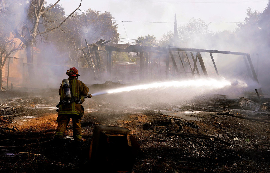Description of . A firefighter cools off some hot spots from a four-alarm fire along the 700 block of Seventh Street in San Bernardino August 18, 2013.  The fire displaced dozens of people from an apartment complex.  GABRIEL LUIS ACOSTA/STAFF PHOTOGRAPHER.