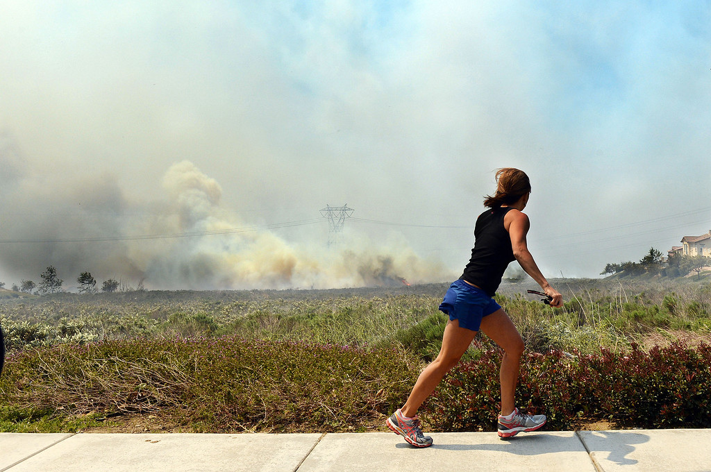 Description of . A resident talks on her phone as she watches the Etiwanda Fire move through Rancho Cucamonga Wednesday. Over 1,000 acres and over a 1,000 homes are under mandatory evacuation as the Etiwanda Fire burns in Rancho Cucamonga Wednesday April 30, 2014. Cause of the fire is unknown and is burning in areas which burned during the Grand Prix Fire in October 2003. (Will Lester/Inland Valley Daily Bulletin)