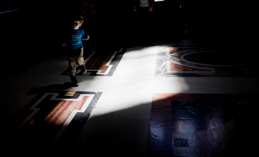 Description of . A child plays inside St. Peter's Basilica at the Vatican, Thursday, April 24, 2014. Hundred thousands of pilgrims and faithful are expected to reach Rome to attend the scheduled April 27 ceremony at the Vatican in which Pope Francis will elevate in a solemn ceremony John XXIII and John Paul II to sainthood. (AP Photo/Alessandra Tarantino)