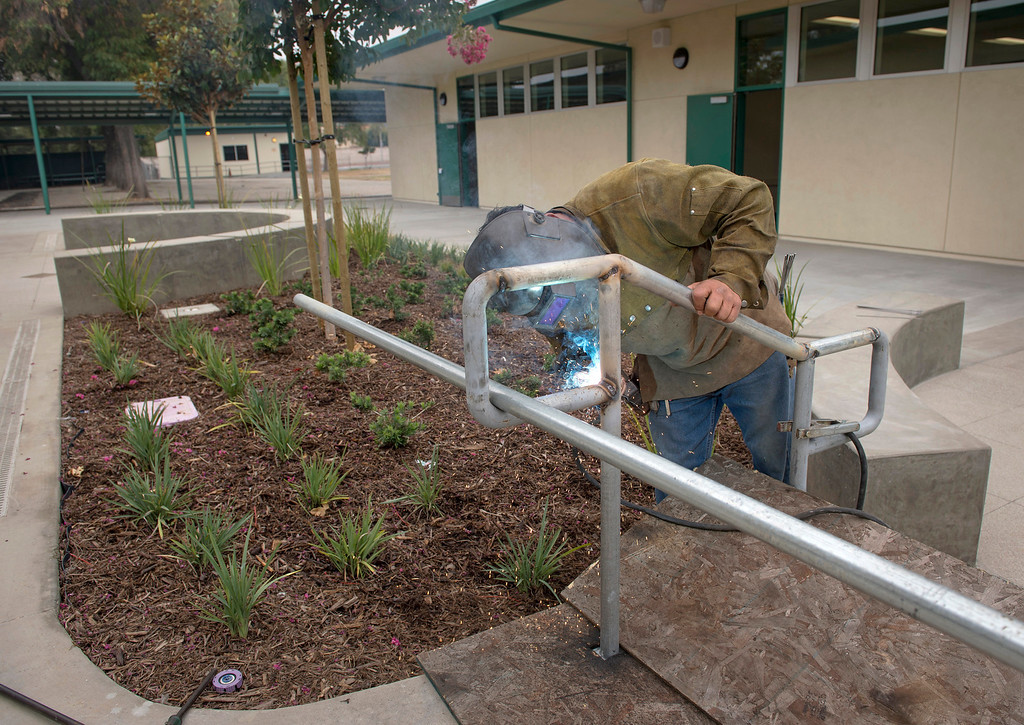 Description of . A worker welds new handrails at Rowland Elementary School's newly remodeled campus August 7, 2013.   (SGVN/Staff photo by Leo Jarzomb)