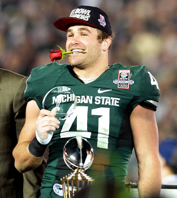 Description of . Michigan State's Kyler Elsworth celebrates as he holds a rose in his mouth after defeating Stanford 24-20 during the 100th Rose bowl game in Pasadena, Calif., on Wednesday, Jan.1, 2014. 