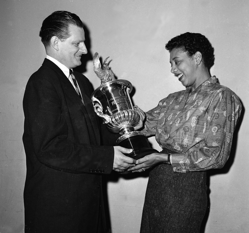 Description of . Althea Gibson, Wimbledon and U.S. Open champion, is presented the Frederick C. Miller trophy for outstanding female athlete of 1957 in New York City on Feb. 15, 1958.  At left is judge Robert Cannon, of Milwaukee.  (AP Photo)