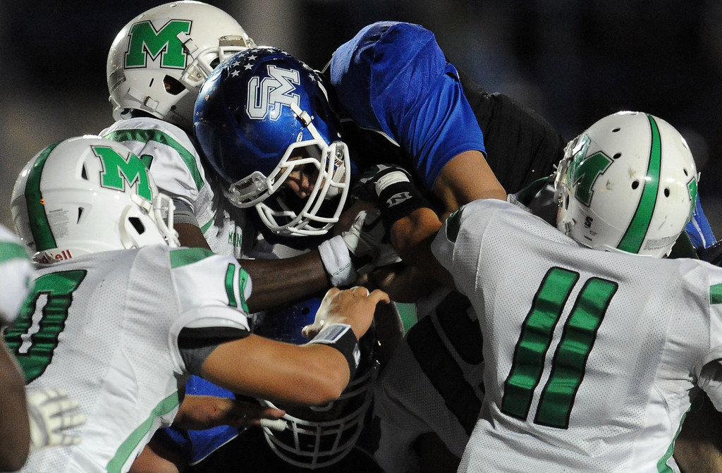 Description of . Monrovia defense stops San Marino quarterback Andrew Ferraco in the first half of a prep football game at Monrovia High School in Monrovia, Calif., on Friday, Nov. 8, 2013.    (Keith Birmingham Pasadena Star-News)
