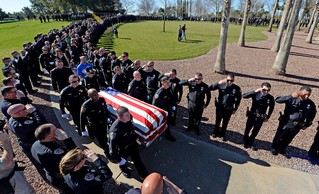 Description of . Riverside police department officers salute as they line the walk as the casket of slain officer Michael Crain in brought in for services at Riverside National Cemetery Wednesday.  Funeral services for Riverside police officer Michael Crain February 13, 2013 at Riverside National Cemetery. Crain was killed February 7, Christopher Dorner is suspected in the shooting death of the officer. (Staff photo by Will Lester)