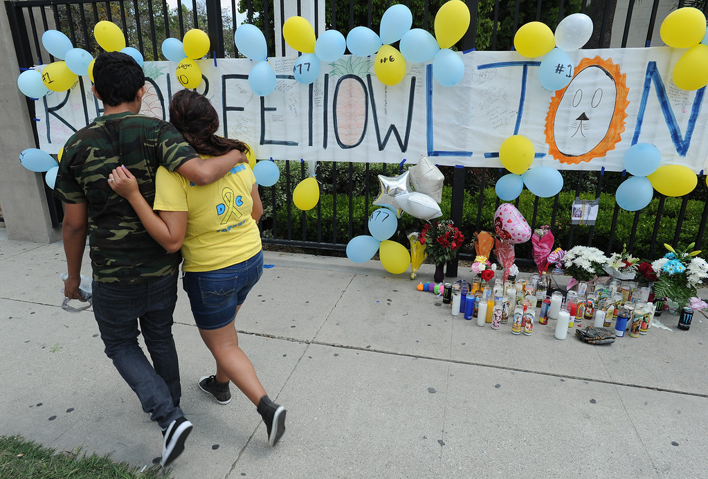 Description of . Jasmine Revelos,17, and Jorge Padilla,17, walk away after paying their respects at the memorial of their classmate. Students at El Monte High School brought flowers, candles and other items in remembering Adrian Castro, a Senior student who was killed in bus crash in Northern California that took the lives of 10 people. El Monte, CA. 4/13/2014(Photo by John McCoy / Los Angeles Daily News)