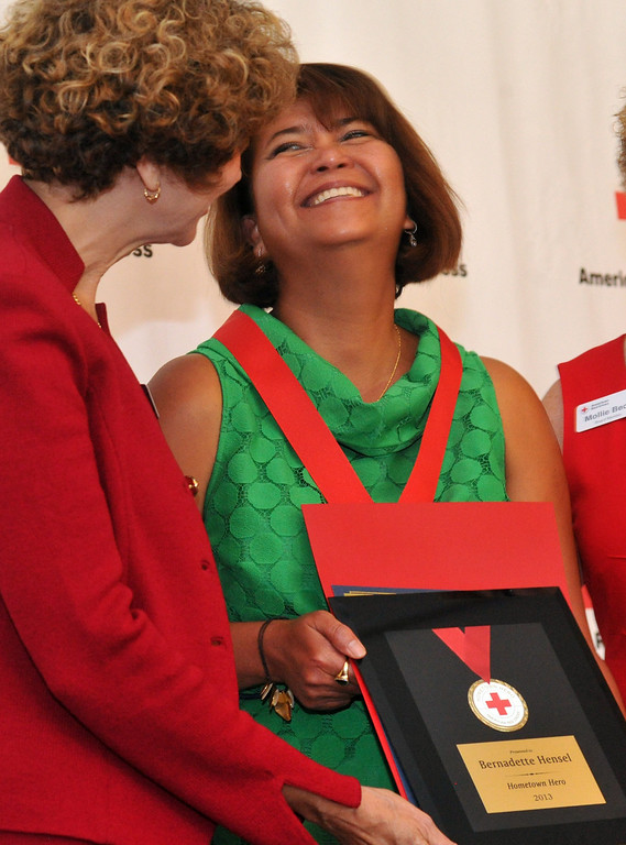 Description of . Bernadette Hensel, right, reacts as she is honored during the Rio Hondo Chapter of the American Red  Hometown Heroes luncheon at the Quiet Cannon in Montebello on Thursday June 27, 2013. (SGVN/Staff Photo by Keith Durflinger)