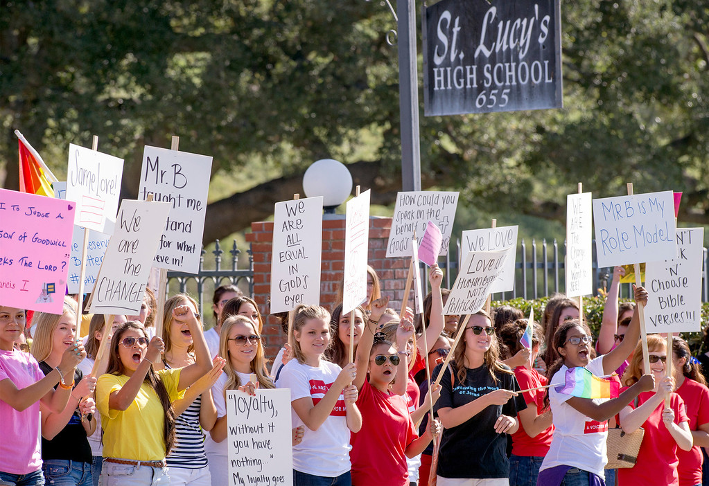 Description of . St. Lucy's Priory High School students and alumni protest the dismissal of longtime teacher Ken Bencomo at the Glendora, Calif. campus August 8, 2013.  Bencomo was  terminated from the all-girls private parochial school after a photo of his marriage to his same-sex partner was published in a local newspaper.  (SGVN/Staff photo by Leo Jarzomb)