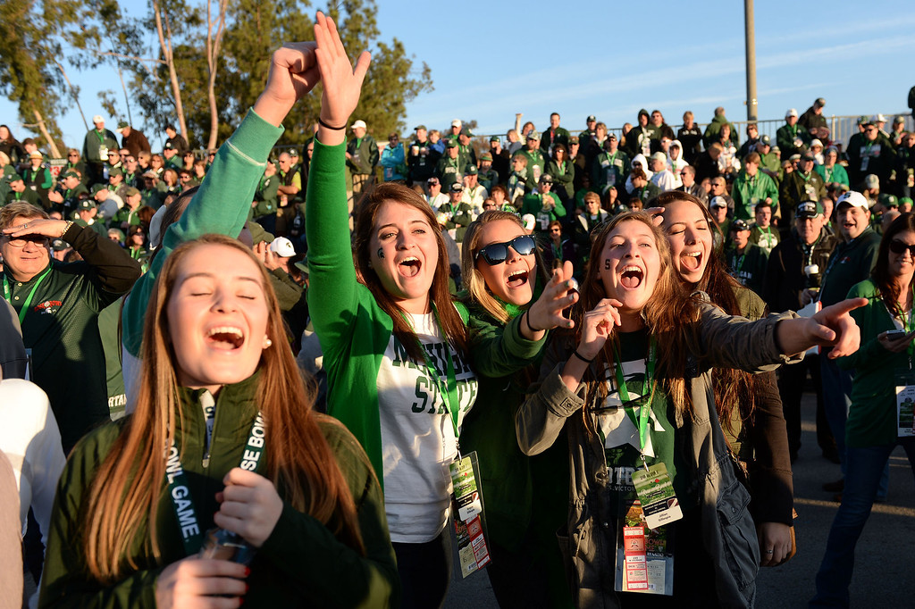 Description of . Michigan State fans cheer during the 2014 Rose Parade in Pasadena, CA January 1, 2014.(Keith Durflinger/San Gabriel Valley Tribune)