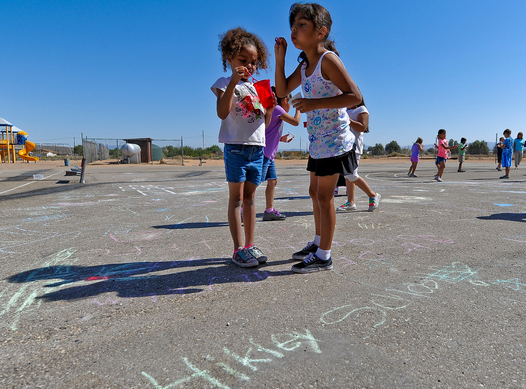 Description of . First-graders Ariel Gibbs, 6, left, and Carmela Morales, 7, right blow bubbles during a fun activity on the final day of school at Hinkley School in Hinkley, Calif. on Thursday, June 6, 2013. Hinkley School is closing for good at the end of the 2012-2013 school year. (Rachel Luna / San Bernardino Sun)