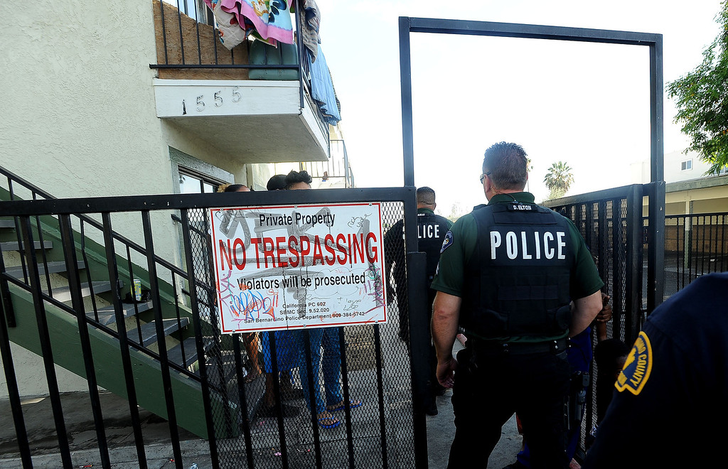 Description of . Police enter the Evergreen Apartments along the 1500 block of Pumalo Street during a county wide police sweep in San Bernardino August 2, 2013. GABRIEL LUIS ACOSTA/STAFF PHOTOGRAPHER.