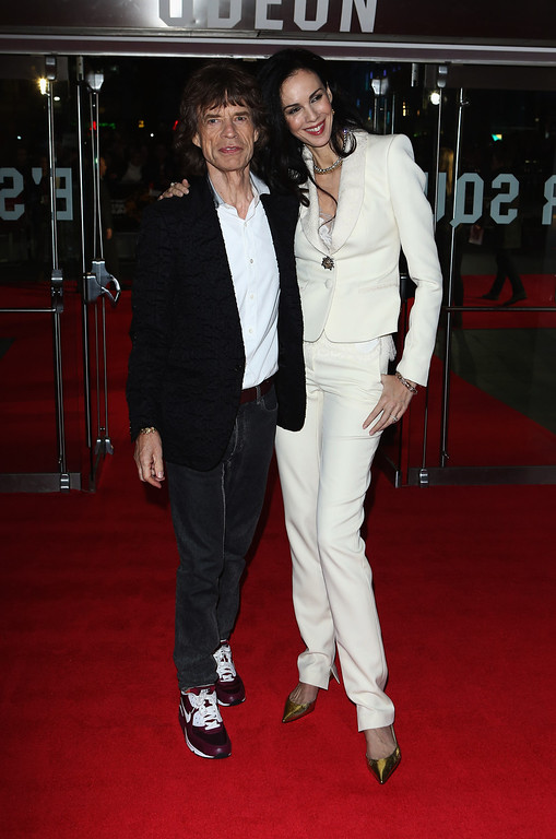 Description of . Mick Jagger of the Rolling Stones and L'Wren Scott attend the Premiere of 'Crossfire Hurricane' during the 56th BFI London Film Festival at Odeon Leicester Square on October 18, 2012 in London, England.  (Photo by Tim Whitby/Getty Images for BFI)