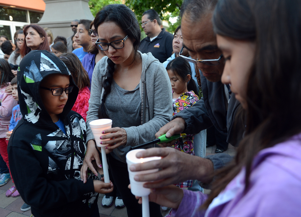 Description of . 0508_NWS_IDB_L-SAMMY-01-JCM (Jennifer Cappuccio Maher/Staff Photographer) Victoria Rivera, of Chino, center, helps her son Ethyn, 8, with his candle as friends and family attend a candlelight vigil for Samantha Padilla Tuesday, May 7, 2013, near the corner of Euclid Ave and Schaefer Ave in Chino. Padilla passed away April 30 from injuries sustained during a car accident.