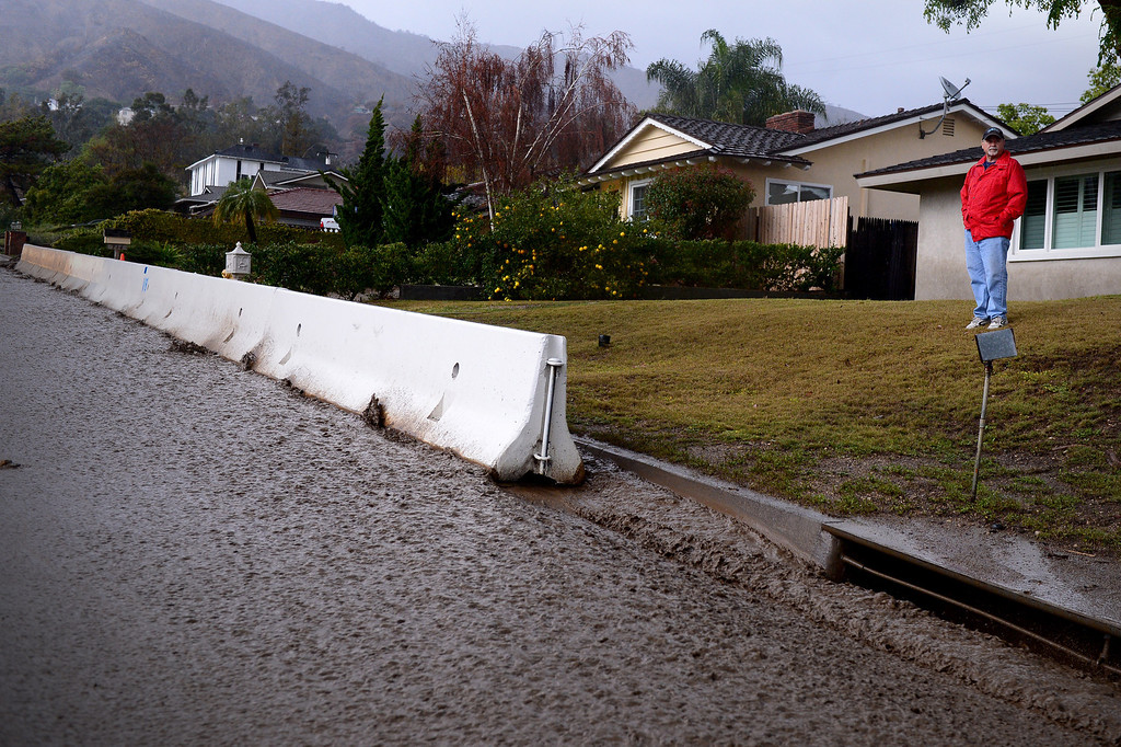 Description of . Resident Bob Roset keeps his eye on swift water rushing down Rainbow Drive in Glendora as the rainstorm starts up again Saturday afternoon, March 1, 2014. The neighborhood sits below the Colby Fire burn area. Resident Tom Tice said this was the most water and mud he's seen in three days of the storm. (Photo by Sarah Reingewirtz/Pasadena Star-News)