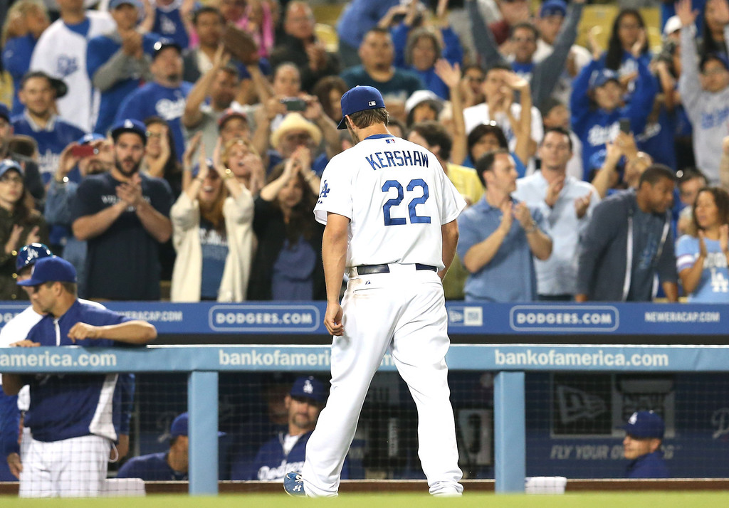 Description of . Starting pitcher Clayton Kershaw #22 of the Los Angeles Dodgers returns to the dugout as he is reilieved in the ninth after pitching 8 2/3 shutout innings against the Washington Nationals at Dodger Stadium on May 14, 2013 in Los Angeles, California.  The Dodgers won 2-0.  (Photo by Stephen Dunn/Getty Images)