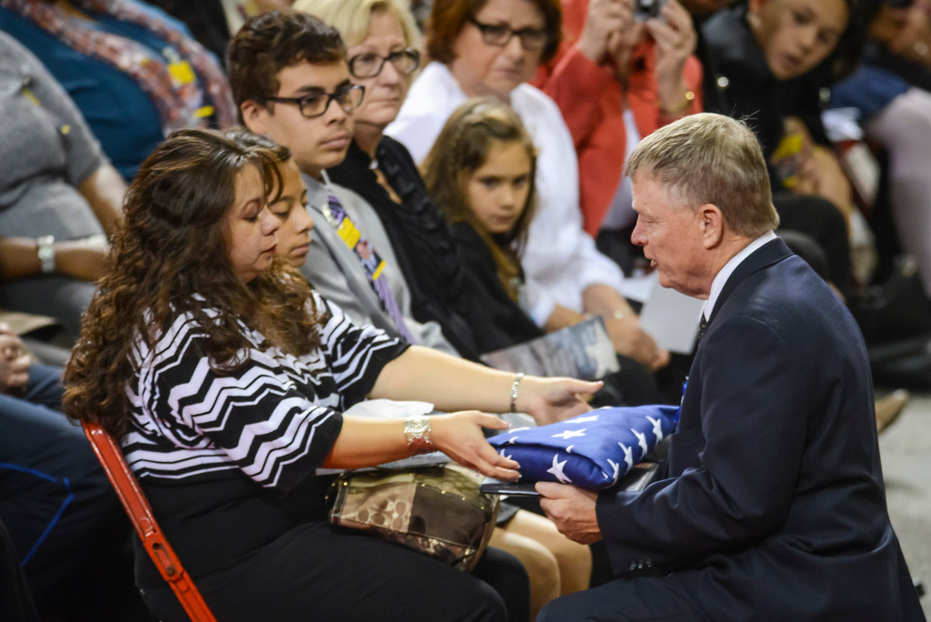 Description of . Acting Secretary of U.S. Homeland Security, Ran Beers presents a flag to Ana Hernandez, wife of slain TSA officer Gerardo Hernandez at the Los Angeles Sports Arena Tuesday, November 12, 2013.  A public memorial was held for Officer Gerardo who was killed at LAX when a gunman entered terminal 3 and opened fire with a semi-automatic rifle.  ( Photo by David Crane/Los Angeles Daily News )