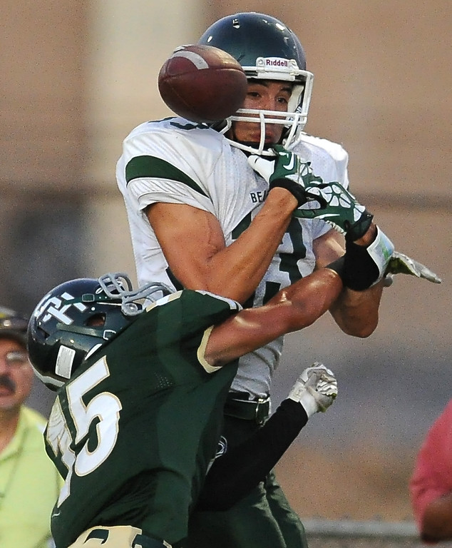 Description of . Bonita's Josh Peiffer (15) defends as he knocks the ball out of Bonita's Dimas Diaz (13) hands in the first half of a prep football game at Covina District Field in Covina, Calif. on Friday, Sept. 6, 2013.   (Photo by Keith Birmingham/Pasadena Star-News)