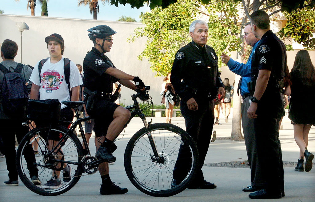 Description of . South Pasadena Police Chief, Arthur Miller, center, with his police officers talk to Superintendent of South Pasadena Unified School District  Dr. Geoff Yantz, on first day back to school Thursday, August 21, 2014. This the the campus where a 16- and 17-year-old boy allegedly planned a mass shooting to kill three staff members and as many students as possible, Police Chief Arthur Miller said. The Los Angeles County District Attorney's Office on Wednesday charged both boys with one count of making criminal threats. The D.A. has not charged the teens for conspiracy to commit a mass shooting, just a shooting. (Photo by Walt Mancini/Pasadena Star-News)