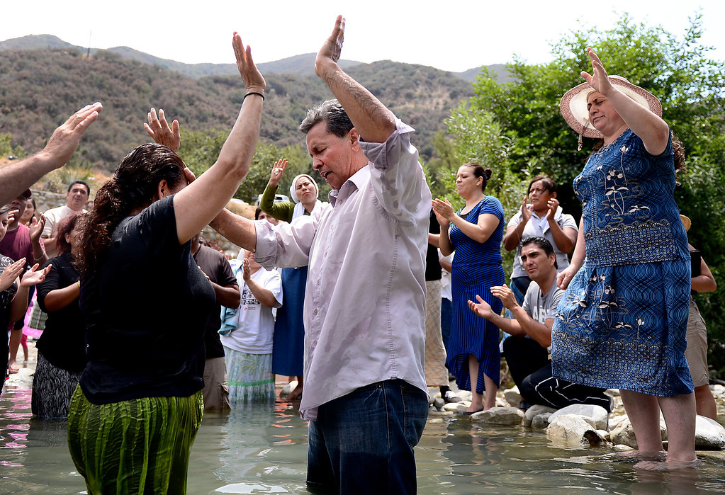 Description of . Pastor Jesus Rodriguez, of Iglesia del Dios Vivo in La Puente, holds baptisms in the San Gabriel River along the East Fork of the Angeles National Forest Saturday, July 20, 2013. The Urban Conservation Corps educates people visiting the East Fork of the San Gabriel River in the Angeles National Forest. Although the Urban Conservation Corps says their river trash count studies show less trash the area is still littered with garbage. (SGVN/Staff Photo by Sarah Reingewirtz)
