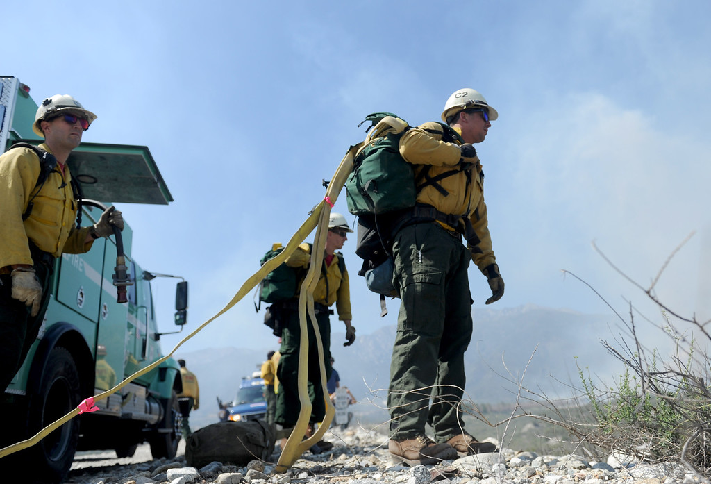 Description of . U.S. Forest Service Firefighters battle the Etiwanda Fire as it moves through Rancho Cucamonga,Ca., Wednesday. The brush fire burned over 1,000 acres threatening homes, forcing residents to evacuate and schools to close. (Photo by John Valenzuela/Inland Valley Daily Bulletin)