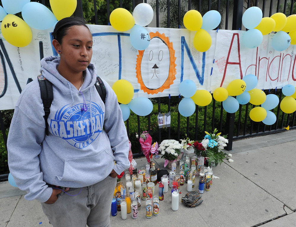 Description of . Bryana Ruiz,17, is an 11th grade student, and fellow athlete of Castro. Students at El Monte High School brought flowers, candles and other items in remembering Adrian Castro, a Senior student who was killed in bus crash in Northern California that took the lives of 10 people. El Monte, CA. 4/13/2014(Photo by John McCoy / Los Angeles Daily News)