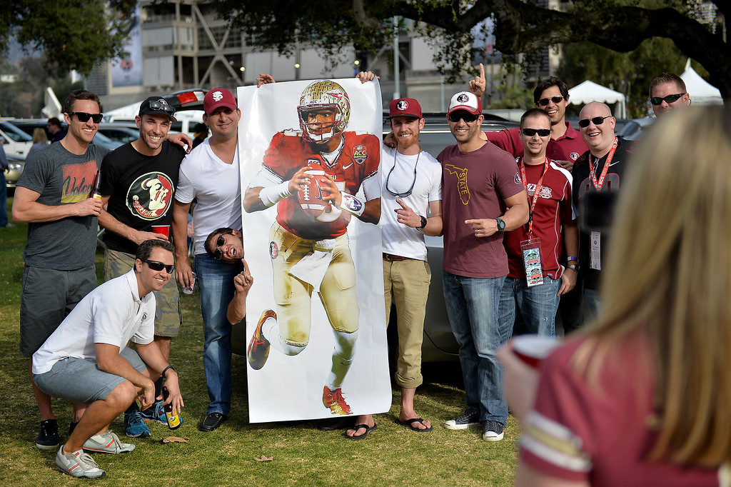 Description of . Florida State fans take a picture next to a poster of Jameis Winston before the BCS game at the Rose Bowl, Monday, January 6, 2014. (Photo by Michael Owen Baker/L.A. Daily News)