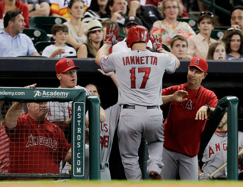 Description of . HOUSTON, TX - SEPTEMBER 14:  Chris Iannetta #17 of the Los Angeles Angels of Anaheim receives high-fives from the bench after hitting a home run in the third inning against the Houston Astros at Minute Maid Park on September 14, 2013 in Houston, Texas.  (Photo by Bob Levey/Getty Images)