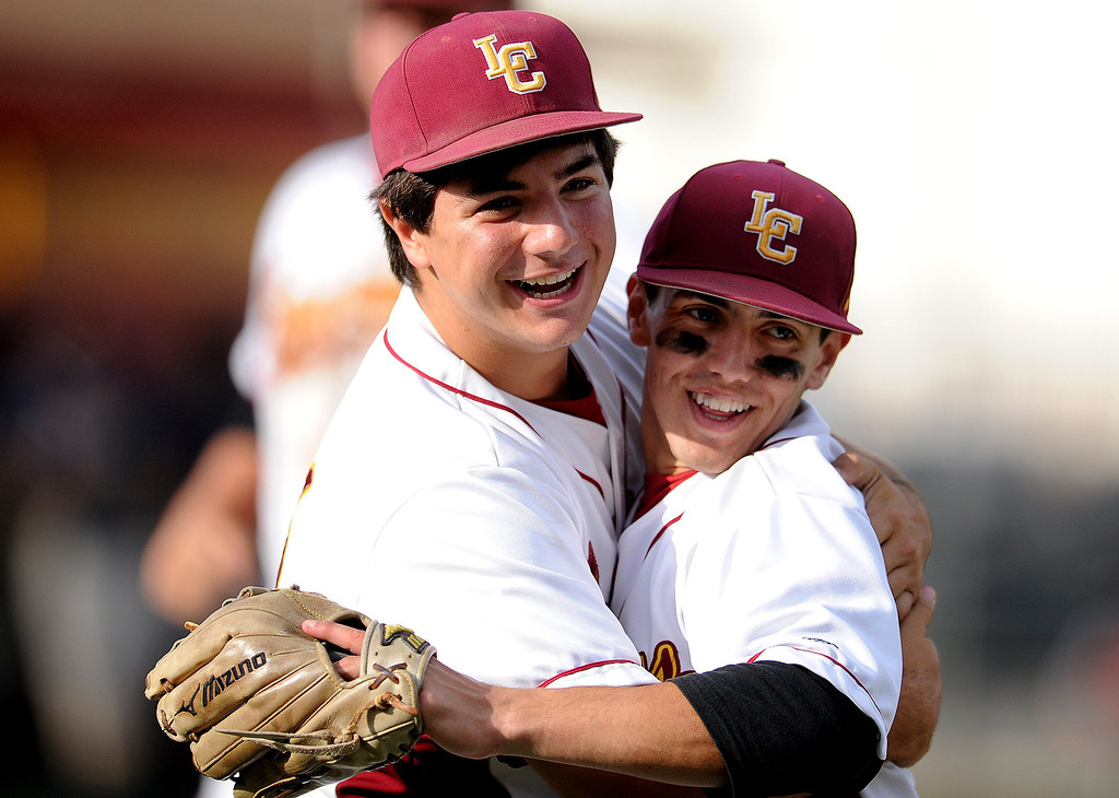 Description of . La Canada's Clayton Herrmann, right, hugs teammate Daniel del Valle after defeating California 4-2 during a CIF-SS playoff baseball game at La Canada High School on Thursday, May 16, 2013 in La Canada, Calif.  (Keith Birmingham Pasadena Star-News)