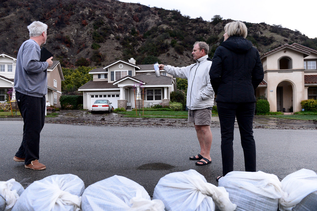 Description of . Dennis and Joann Sanderson walk along their Ridge View Drive street in Azusa early Saturday morning, March 1, 2014 as they stop to talk to neighbor Mark Bryan. The Sanderson's stayed behind mandatory evacuation orders. The neighborhood sits below the Colby Fire burn area. (Photo by Sarah Reingewirtz/Pasadena Star-News)