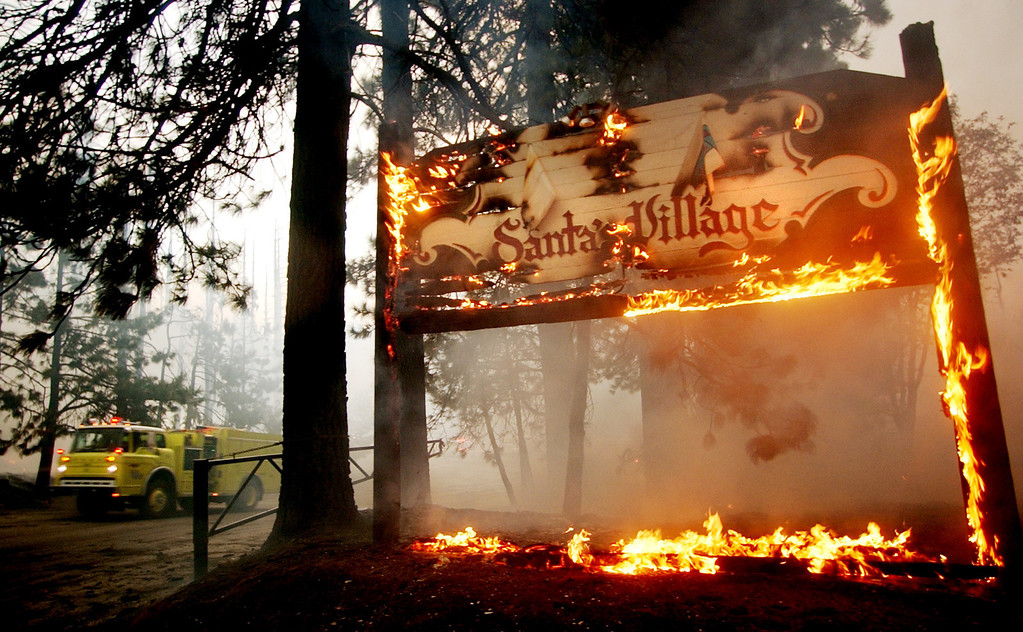 Description of . Ten years ago this month the arson caused Old Fire, fanned by Santa Ana winds burned thousands of acres, destroyed hundreds of homes and caused six deaths. The fire burned homes in San Bernardino, Highland, Cedar Glen, Crestline, Running Springs and Lake Arrowhead and forced the evacuation of thousand of residents. The sign entering Santa's Village in Sky Forest burns during the Old Fire. (Staff file photo/The Sun)